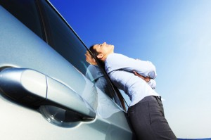 Vrouw rust buiten, leunend over de auto.